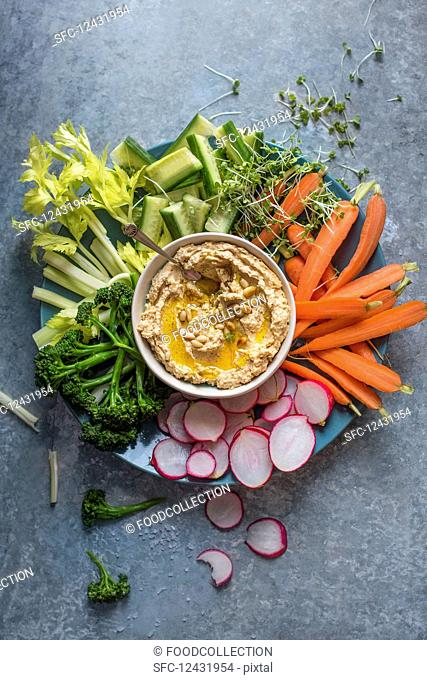 Homemade houmous with olive oil and pinenuts and raw vegetable for dipping