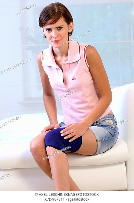 woman checking her knee wearing bandage