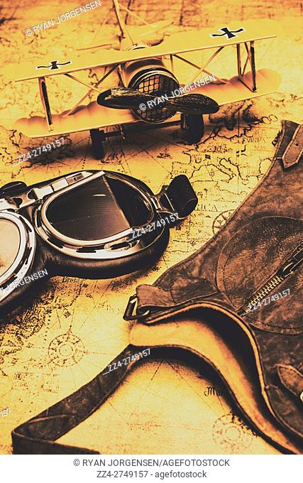 Still life vintage explorer still-life photo of a pilot goggles with leather flight cap and miniature plane on old world map