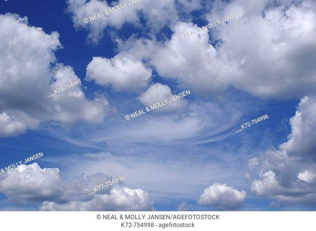 On this beautiful summer day white puffy clouds float around in a deep blue sky