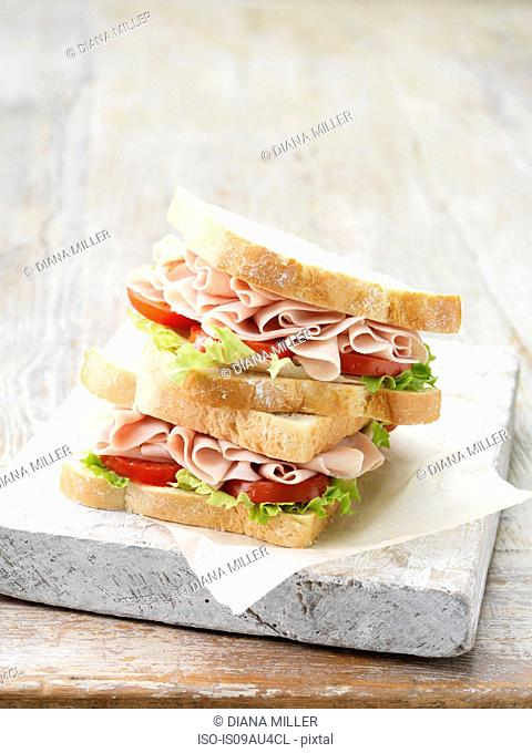Stack of wafer thin ham sandwiches on sliced white bread with salad leaves and tomatoes
