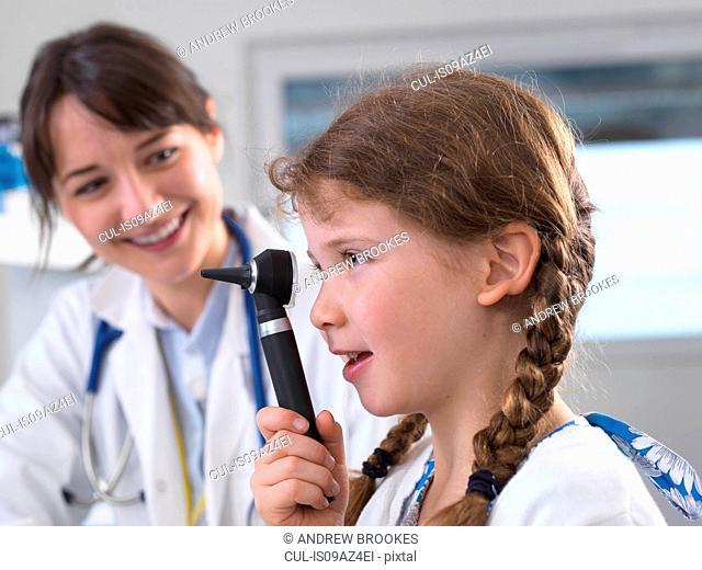 Girl looking through otoscope