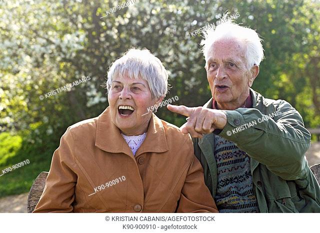 Elderly couple sitting on a bench, looking astonished with open mouth while the senior man pointing with his finger, Island of Amrum, Northfrisian