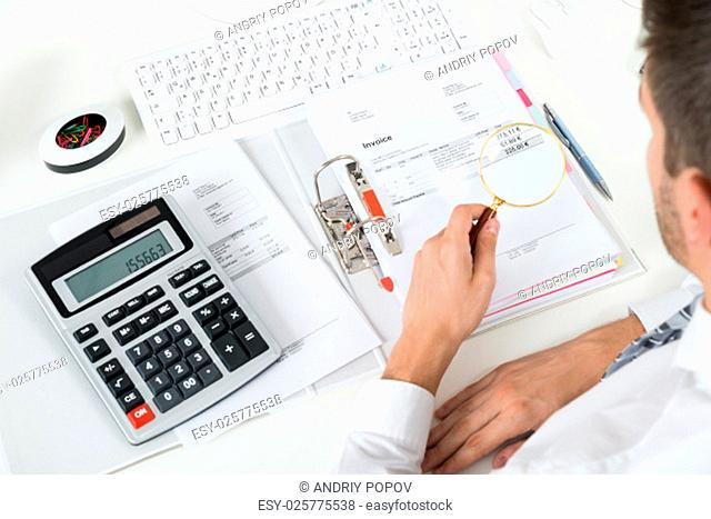 Young Businessman Checking Invoice With Magnifying Glass At Desk
