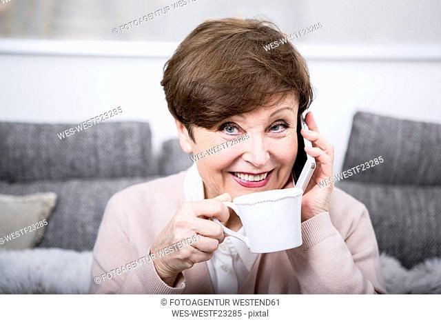 Portrait of a senior woman using smart phone, drinking coffee