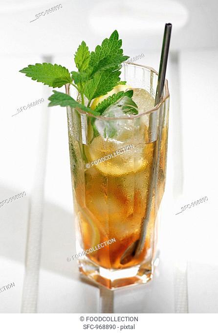 Glass of iced tea with lemon slices and lemon balm