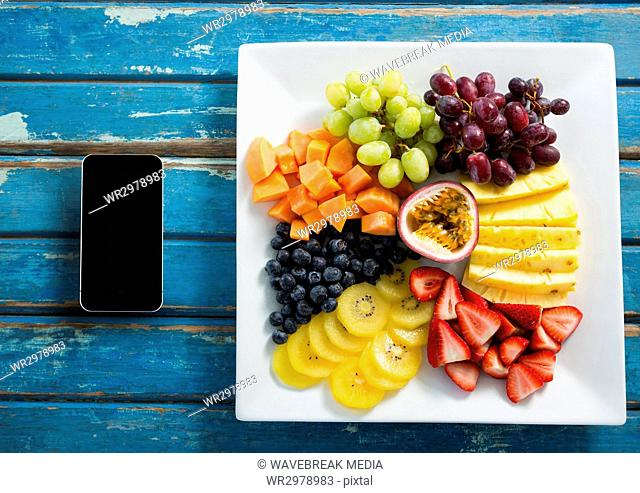 Phone on blue wooden desk with food