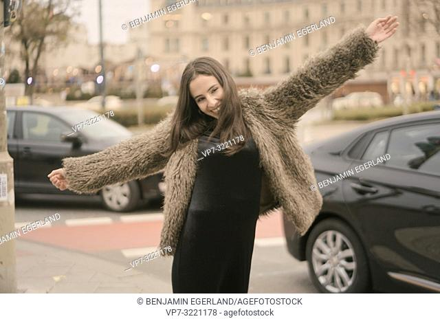 playful happy carefree woman dancing on street in city, next to car traffic, in Munich, Germany
