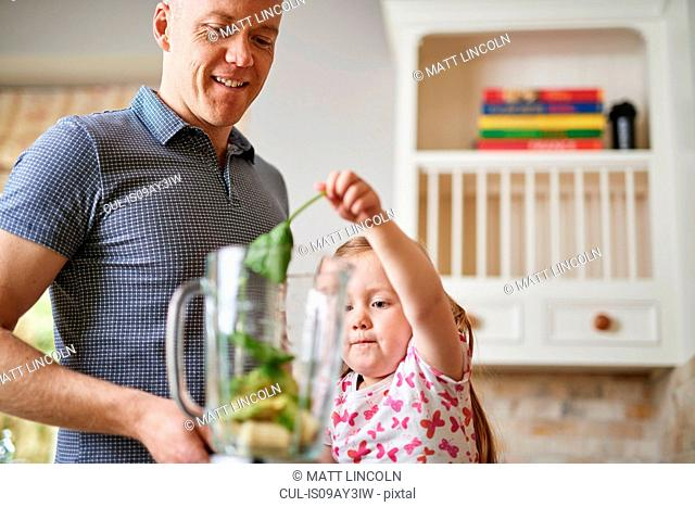 Father and daughter adding ingredients to blender