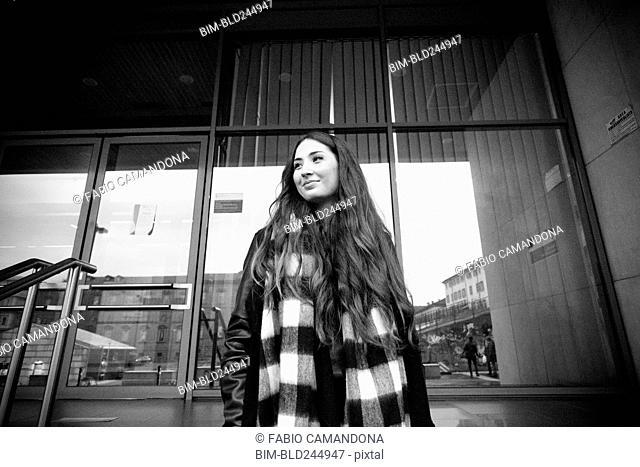 Smiling Caucasian woman standing near building