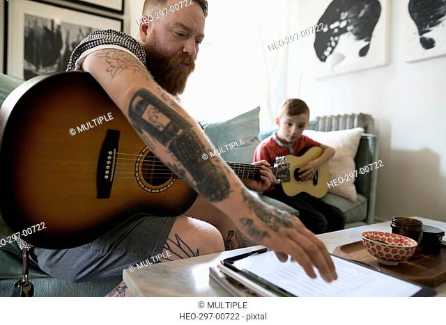 Father with digital tablet teaching son playing guitar in living room