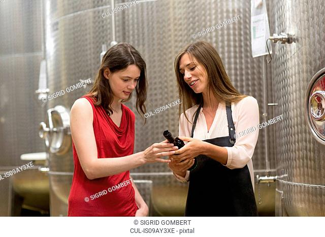 Two young women in wine cellar looking at bottle of wine