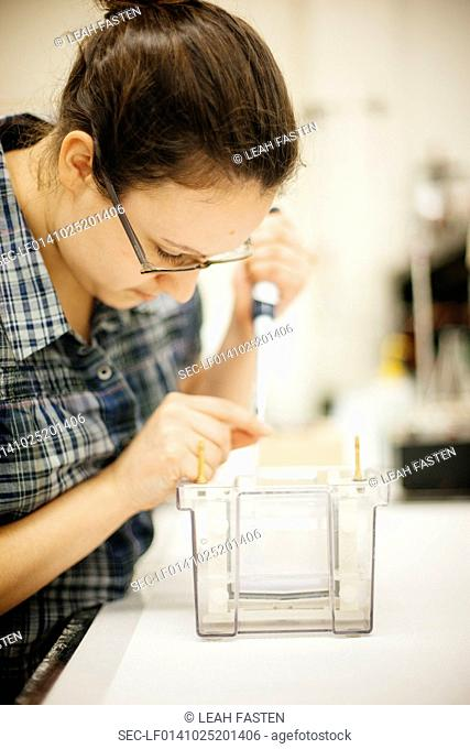 Close-up shot of female lab technician using burette