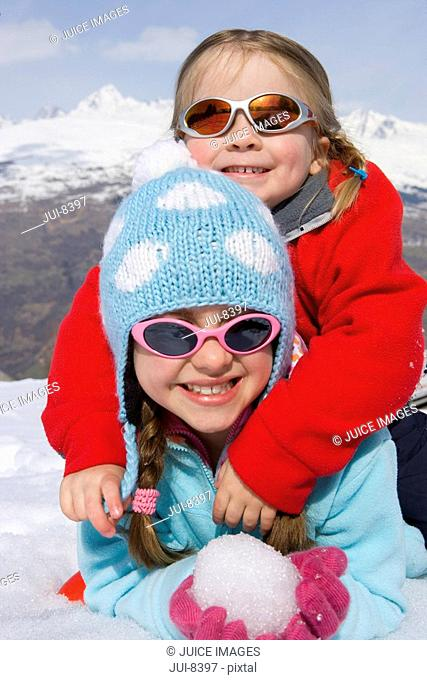 Two girls 6-8 together in snow field, wearing sunglasses, smiling, portrait, mountain range in background