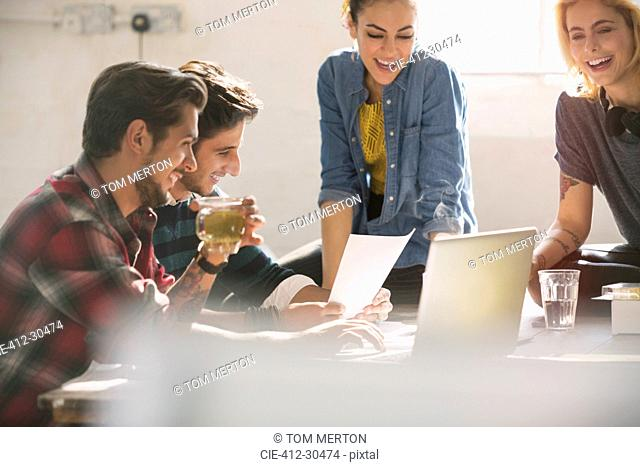Young creative business people working at laptop