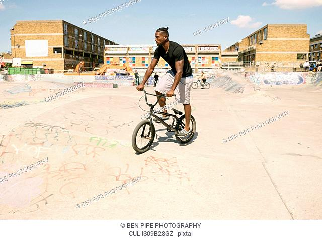 Young man riding BMX bicycle in skatepark