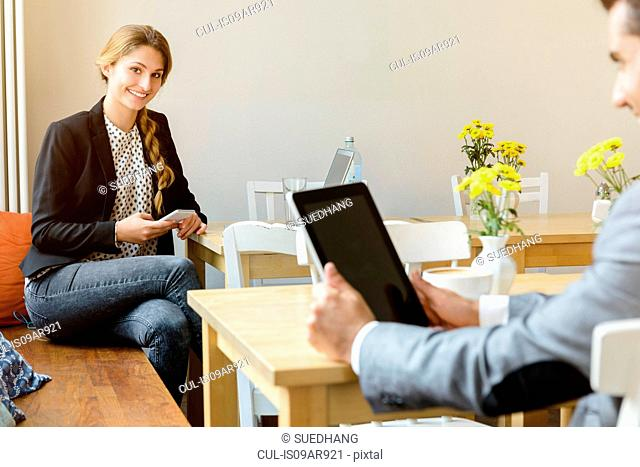 Young woman and man in cafe using laptop and digital tablet