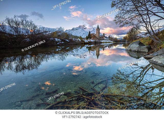 Dawn illuminates the snowy peaks and the bell tower reflected in Lake Sils Engadine Canton of Graubünden Switzerland Europe