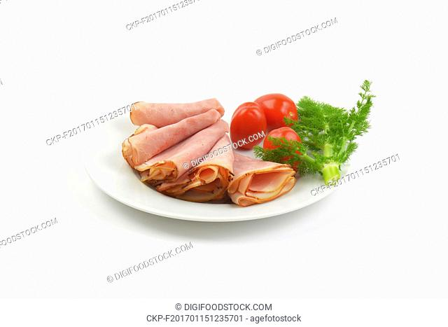 plate of ham slices with fresh dill and cherry tomatoes on white background