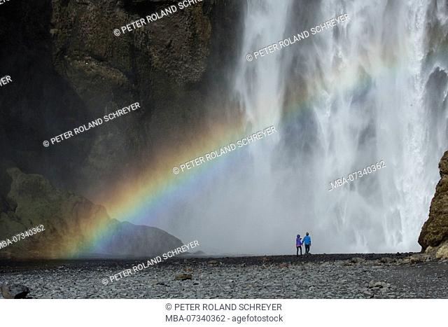 Europe, Northern Europe, Iceland, Skógar, couple standing in front of the mighty Skógafoss in southern Iceland, rainbow