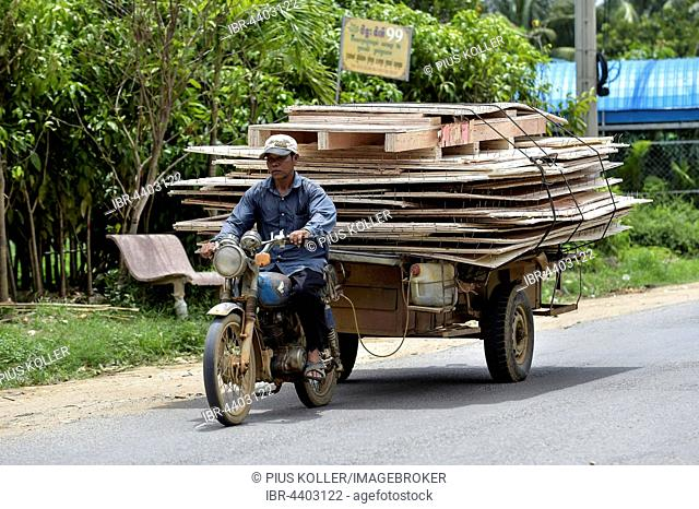 Man with moped and trailer transporting large wooden panels, Phnom Penh Province, Cambodia