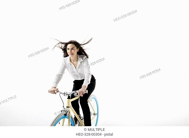 Smiling businesswoman riding bicycle against white background