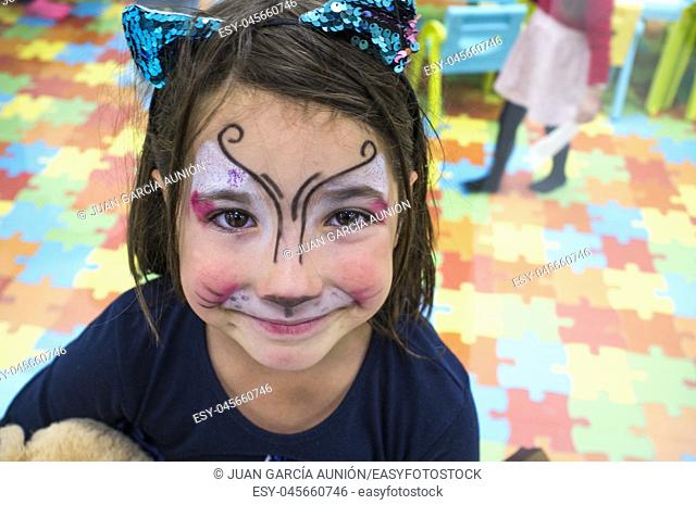 Child girl posing face painted during at Children Playroom. High angle shot
