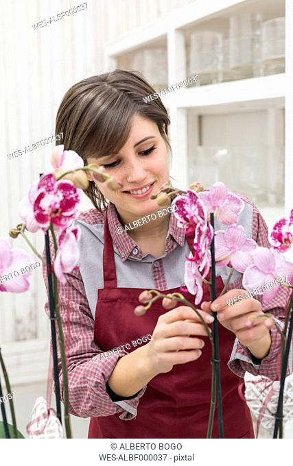 Young female gardener working in greenhouse