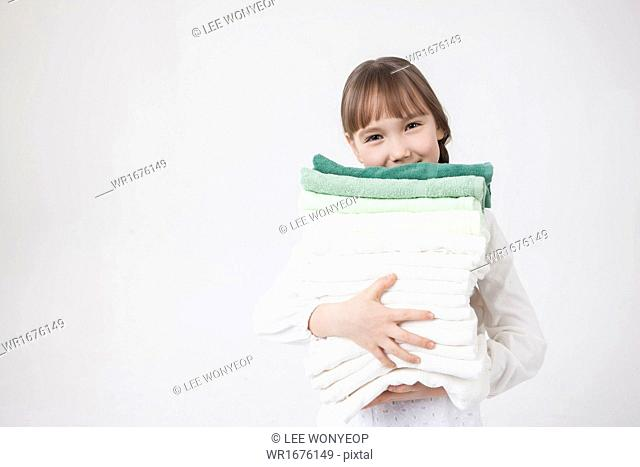 a girl carrying a pile of fresh towels
