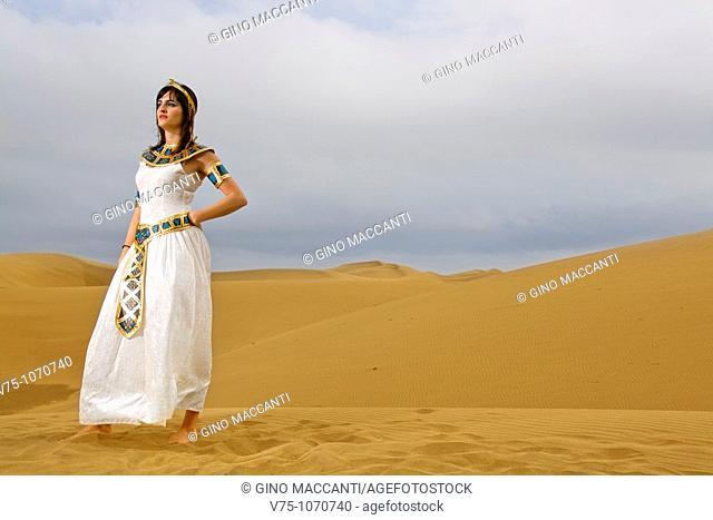Girl dressed like Cleopatra posing on the desert dunes