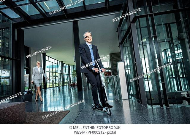 Germany, Stuttgart, Businesswoman with wheeled luggage, man riding scooter at office building