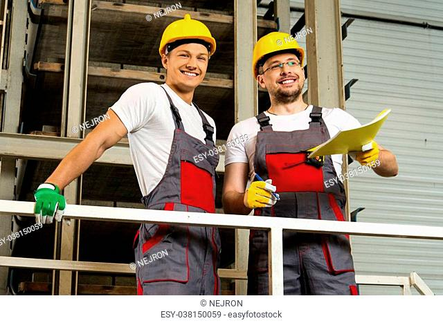 Two positive workers in safety hats on a factory