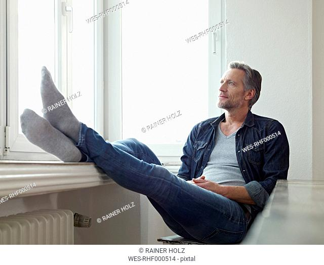 Germany, Cologne, Mature man sitting at window, looking out