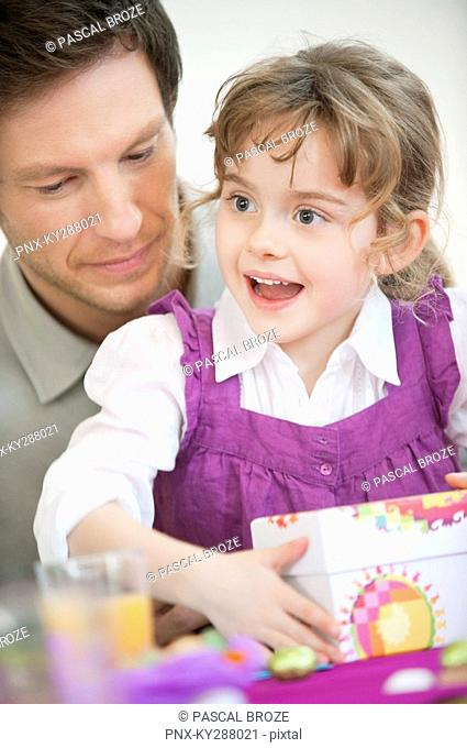 Girl holding her birthday present with her father