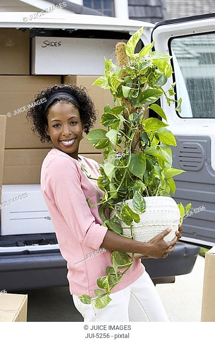 Woman moving house, standing beside van in driveway, carrying pot plant, smiling, portrait