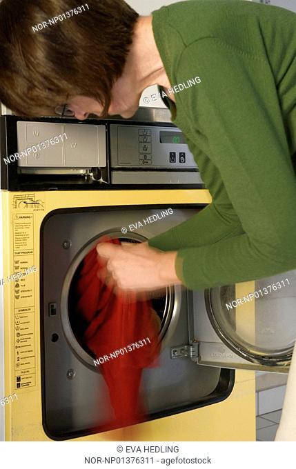 A woman filling a washing machine, Sweden