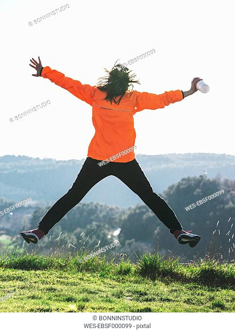 Young female jogger jumping in the air