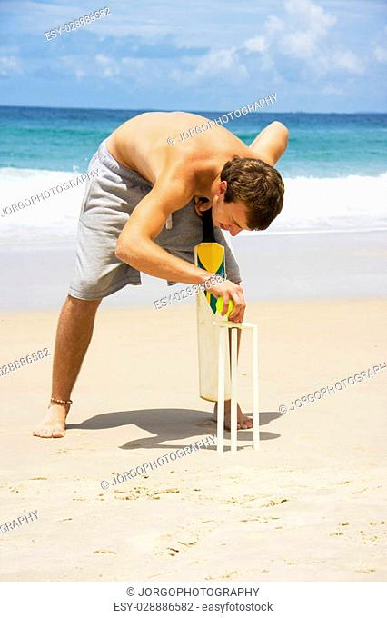Young man with bare chest and shorts balancing bails on beach cricket stumps with sea in background