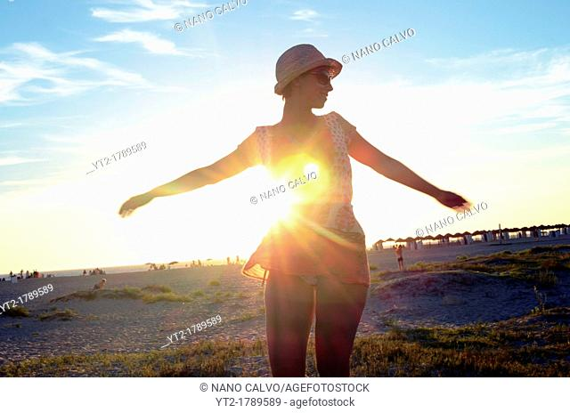 Young girl dances on the beach at sunset