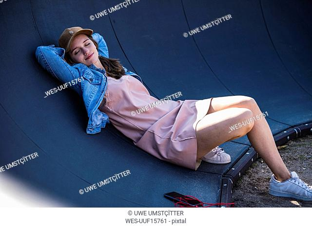 Smiling young woman lying outdoors with closed eyes