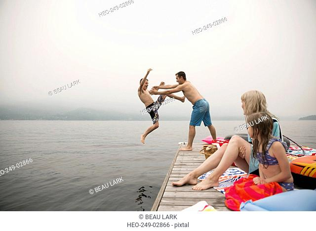 Playful father throwing son into lake from dock