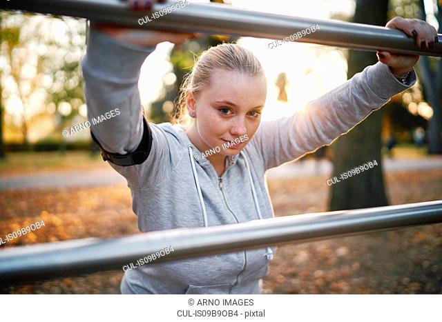 Curvaceous young woman training, portrait leaning against handrail in park