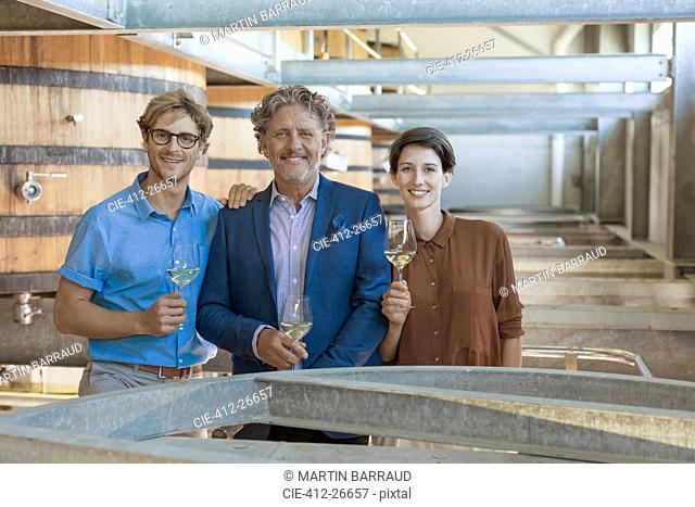 Portrait smiling vintners with white wine in winery cellar