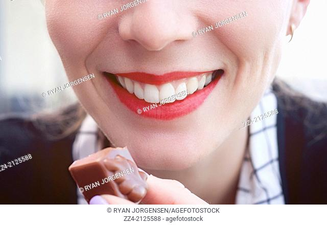 Close portrait on the bright red lips of a beautiful young woman smiling while eating luxury chocolate pieces