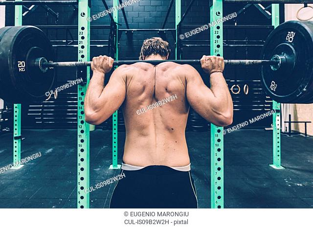 Rear view of male cross trainer weightlifting barbell in gym