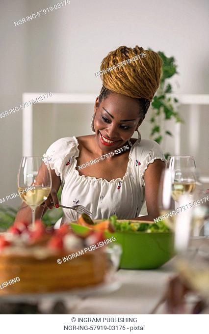 Closeup Of Beautiful African American Woman Eating Healthy Food and Drinking Wine At Home