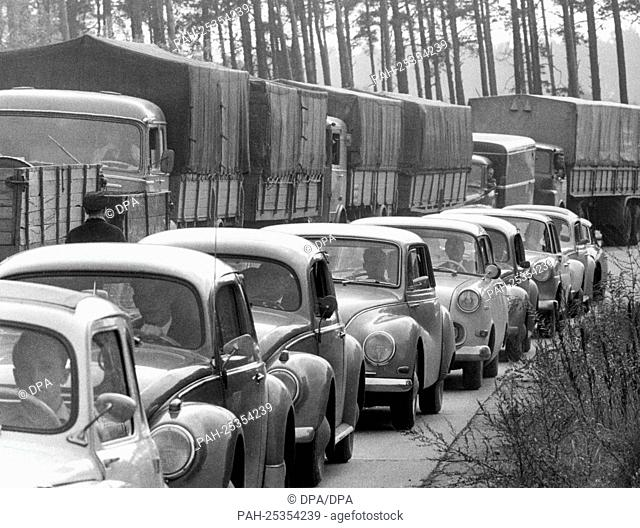 A long traffic jam of private cars next to a held back convoy of the US army at border crossing point Dreilinden on the 11th of October in 1963