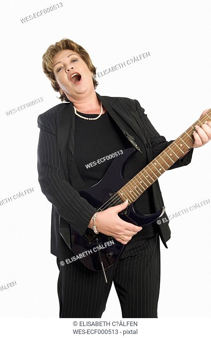 Portrait of woman playing guitar and singing