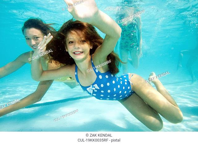Girl underwater, smiling towards camera