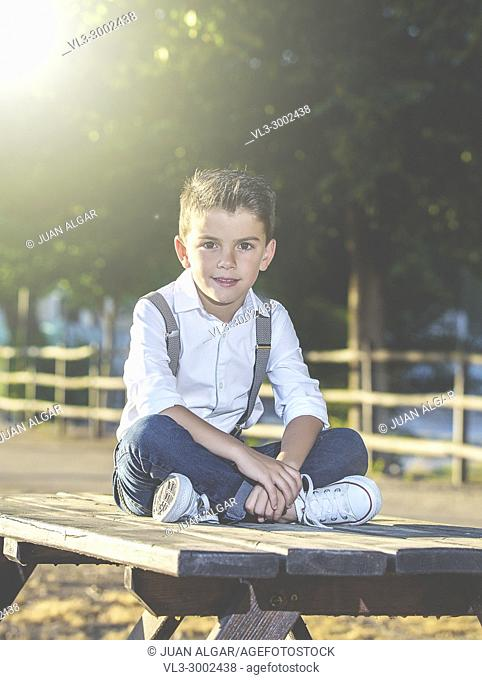 Stylish boy in suspenders and jeans sitting on table in park looking at camera